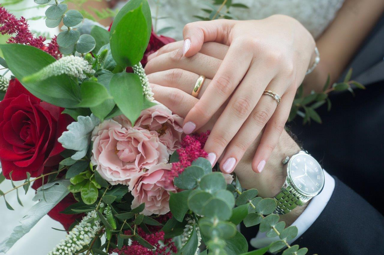 evermore weddings bride groom hands on florals