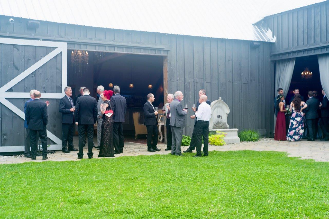 evermore weddings ourdoor shot towards barn featuring guests