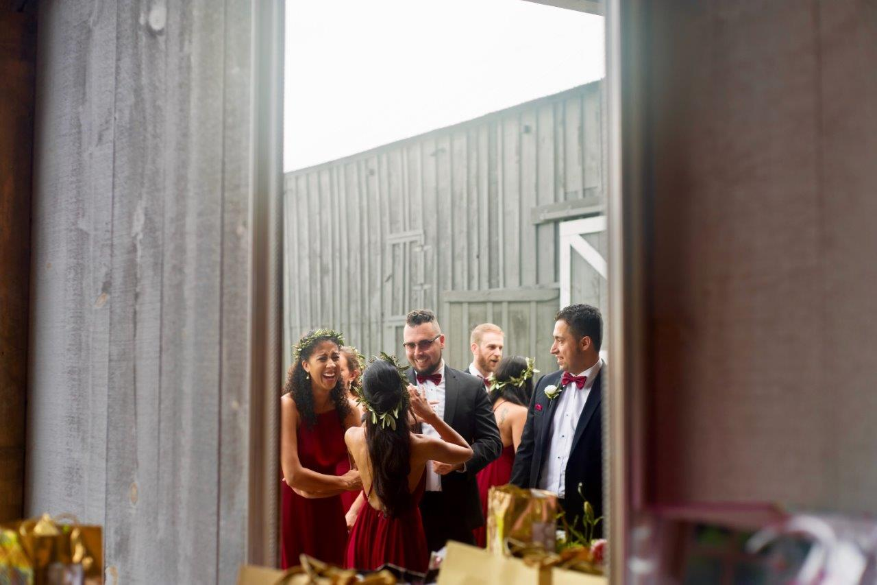 evermore weddings wedding party having fun through barn doors