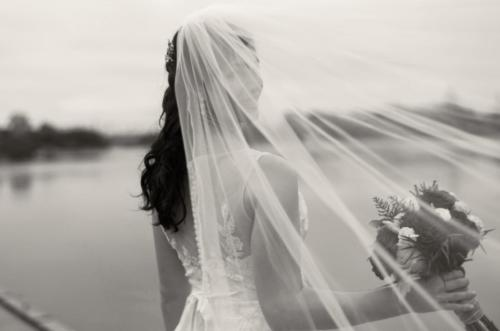 bride behind veil on waterfront
