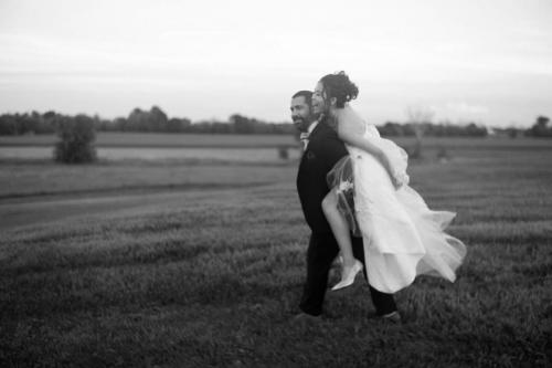 bride on grooms back in feild