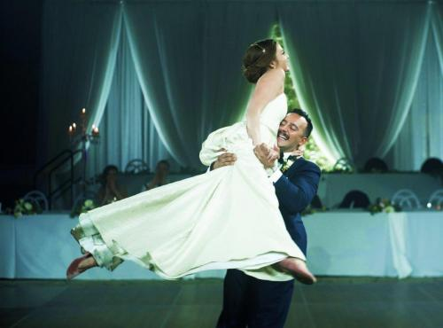 groom lifting bride on dancefloor