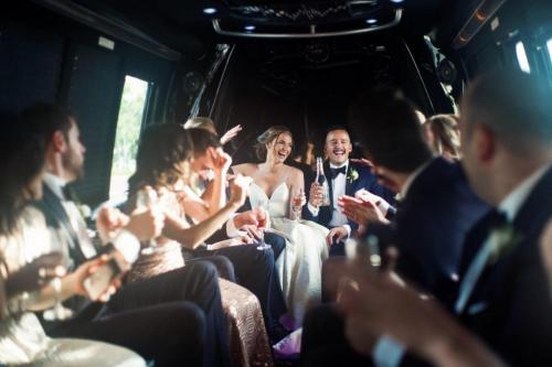 wedding party in limo. bride groom toasting